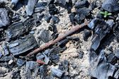 Oude roestige spijker in vuurplaats met kolen en ash — Stockfoto