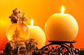 Burning Candles and Snow Globe on Warm Yellow Background — Stock Photo