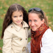 Stock Photo: Mother with little girl in autumn park