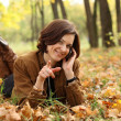 Woman calling by phone in autumn park — Stock Photo #13518529