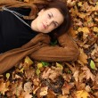 Woman lying on a carpet of leaves in autumn park — Stock Photo #13518537