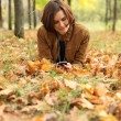 Woman lying on a carpet of leaves in autumn park — Stock Photo #13518543