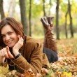 Woman lying on a carpet of leaves in autumn park  — Stock Photo