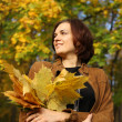 Stock Photo: Beautiful woman with a bouquet of maple leaves