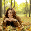 Woman lying on a carpet of leaves in autumn park - Stock Photo