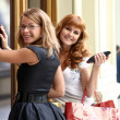Two happy women with shopping in a store — ストック写真