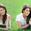 Two women lying on grass field at the park — Stock Photo