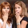 Two young beautiful women are very surprised - Stock Photo