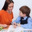 Mother or teacher helping kid with schoolwork - Stock Photo