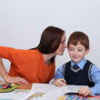 Mother or teacher helping kid with schoolwork — Stock Photo #14404665