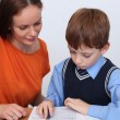 Mother or teacher helping kid with schoolwork — Stok fotoğraf