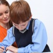 Mother or teacher helping kid with schoolwork — Stock Photo #14404751