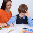 Mother or teacher helping kid with schoolwork — Stock Photo #14404761