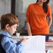 Mother or teacher helping kid with schoolwork — Stock Photo #14404765