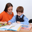 Mother or teacher helping kid with schoolwork - Foto Stock