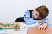 Beautiful little boy sleeping on the table — Stock Photo