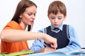 Mother or teacher helping kid with schoolwork — Stock Photo