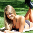 Beautiful sexy woman sunbathes in park  — Stock Photo
