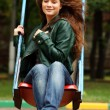 Young woman wearing colourful scarf sitting on a swing in a park - Stockfoto