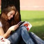 Portrait of young beautiful woman reading magazine — Stock Photo #15853449