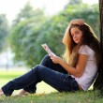 Portrait of young beautiful woman reading magazine — Stock Photo #15853459