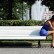 Young woman sitting on a park bench - Stock Photo