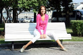 Beautiful young woman sitting on a park bench — Stock Photo