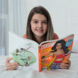 Little girl turning over the pages of magazines — Stock Photo #16315773