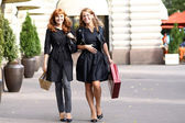 Happy young women walking in the street — Stock Photo
