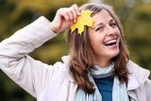 Beautiful woman with a bouquet of maple leaves — Stock Photo