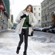 Young woman walking down snow covered street — Stock Photo