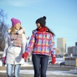 Happy young couple women in winter street — Stock Photo