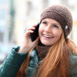 Happy young woman calling by phone - Stock Photo