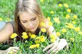 Young woman blows on a dandelion — Stock Photo