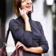 Young happy woman calling by phone on the street - Foto Stock