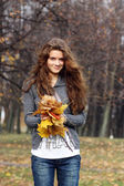 Portrait of a happy woman against yellow leaves — Stock Photo