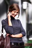 Young happy woman calling by phone on the street — Stock Photo