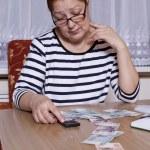 Elderly woman holding money in hand — Stock Photo