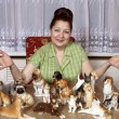 Elderly woman with a collection of porcelain figurines of dogs — Stock Photo