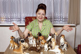 Elderly woman with a collection of porcelain figurines of dogs — Stok fotoğraf