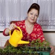Happy senior woman watering can at home — Stock Photo