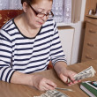 Senior woman counting savings money — Stock Photo #24150001
