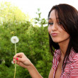 ������, ������: Young woman blows on a dandelion