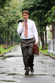 Cheerful young businessman walking on the street — Stock Photo