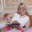 Closeup of senior woman lying in bed reading a book - Foto de Stock