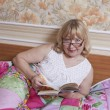 Closeup of senior woman lying in bed reading a book - ストック写真