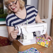 Old woman sews on the sewing machine — Stock Photo