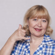 Old beautiful woman making a call me gesture — Stock Photo