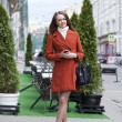 Beautiful young woman in red coat on the street — Foto Stock