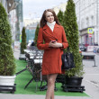 Beautiful young woman in red coat on the street — Stock Photo